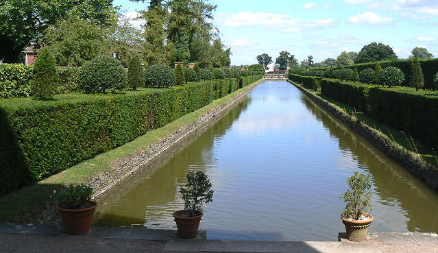 Straight canals with topiary specimens growing through the yew hedges