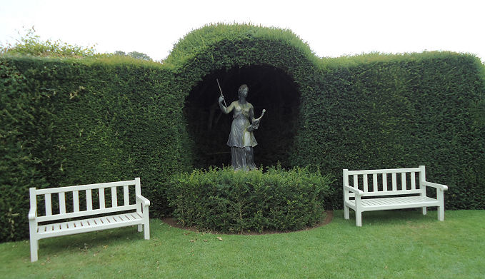 Statue of woman in artistic pose set in a yew niche