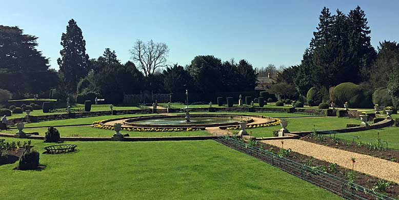 Circular pool with topiary specimens arranged around the edges in a classical style